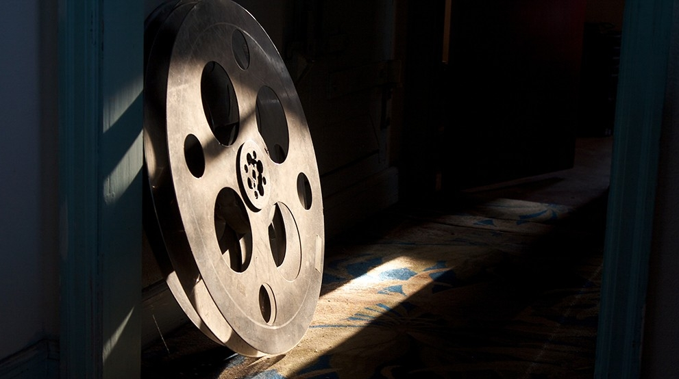 An old film reel sits in a beam of light.