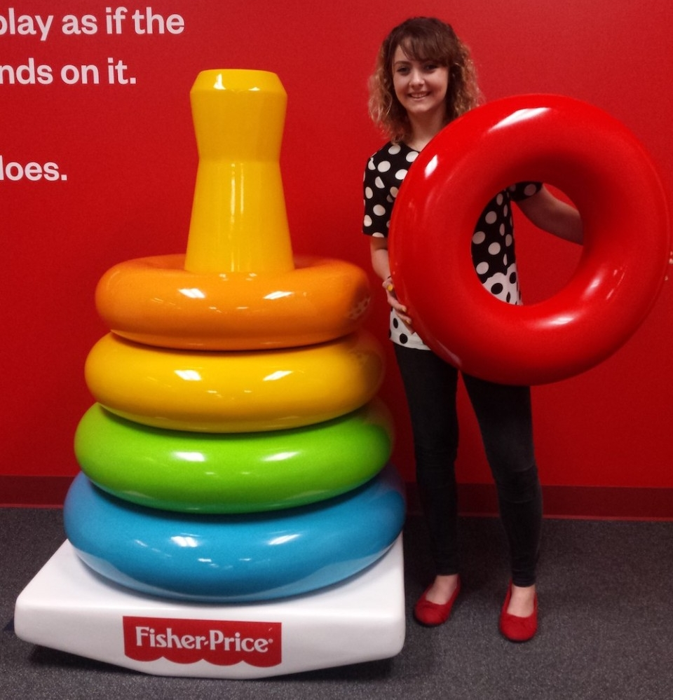 A young woman stands next to jumbo-sized Fisher-Price rainbow stacking rings toy.