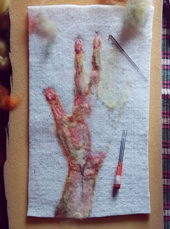 Felt art piece featuring an unfinished hand