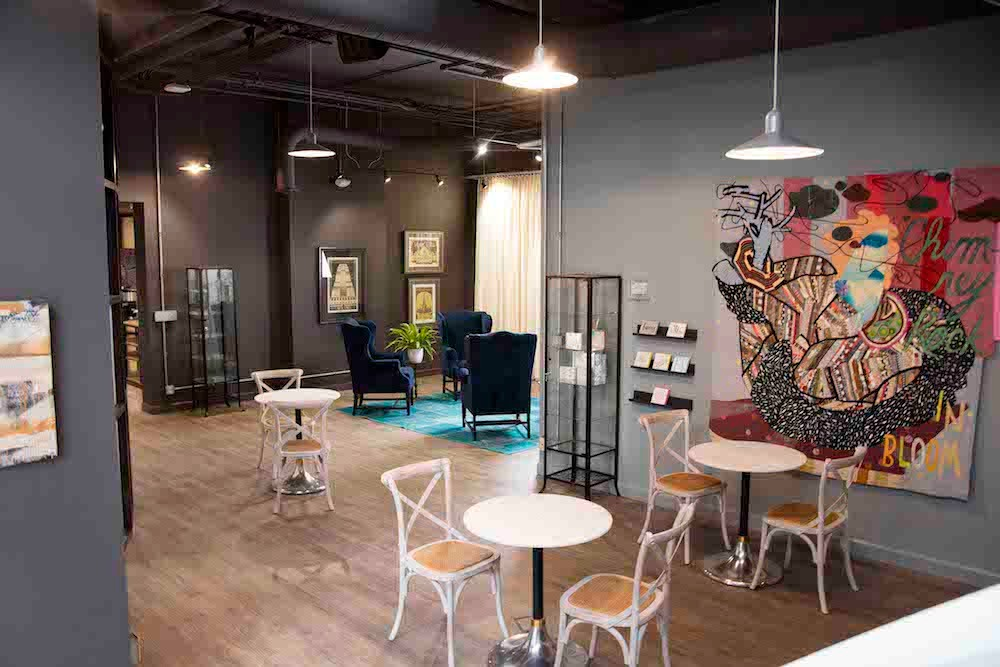 Inside a creative co-working space: cafe tables and chairs, lighting and artwork