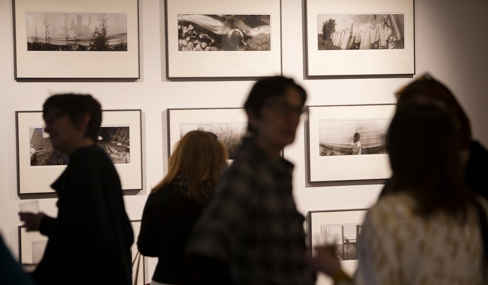 People mingle in an art gallery with framed black and white photographs in the background.