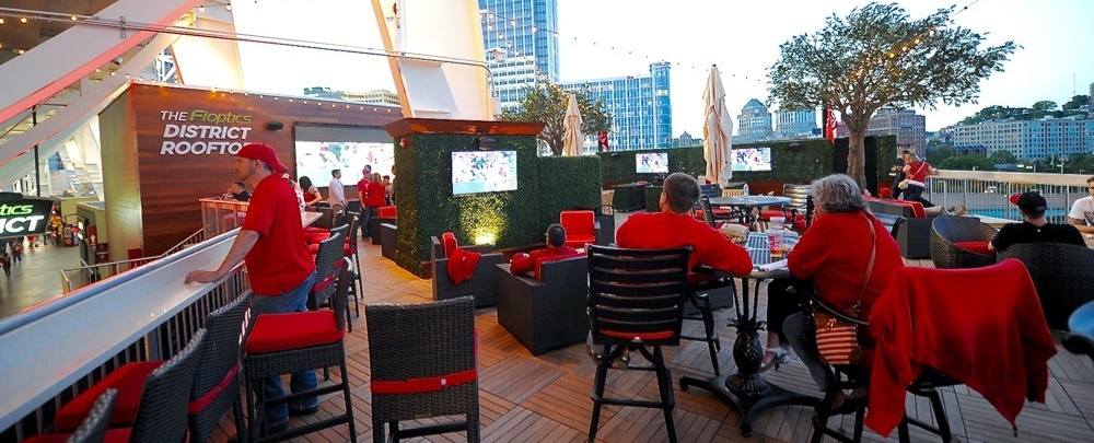 Men and women sit at tables and bar at Great American Ball Park