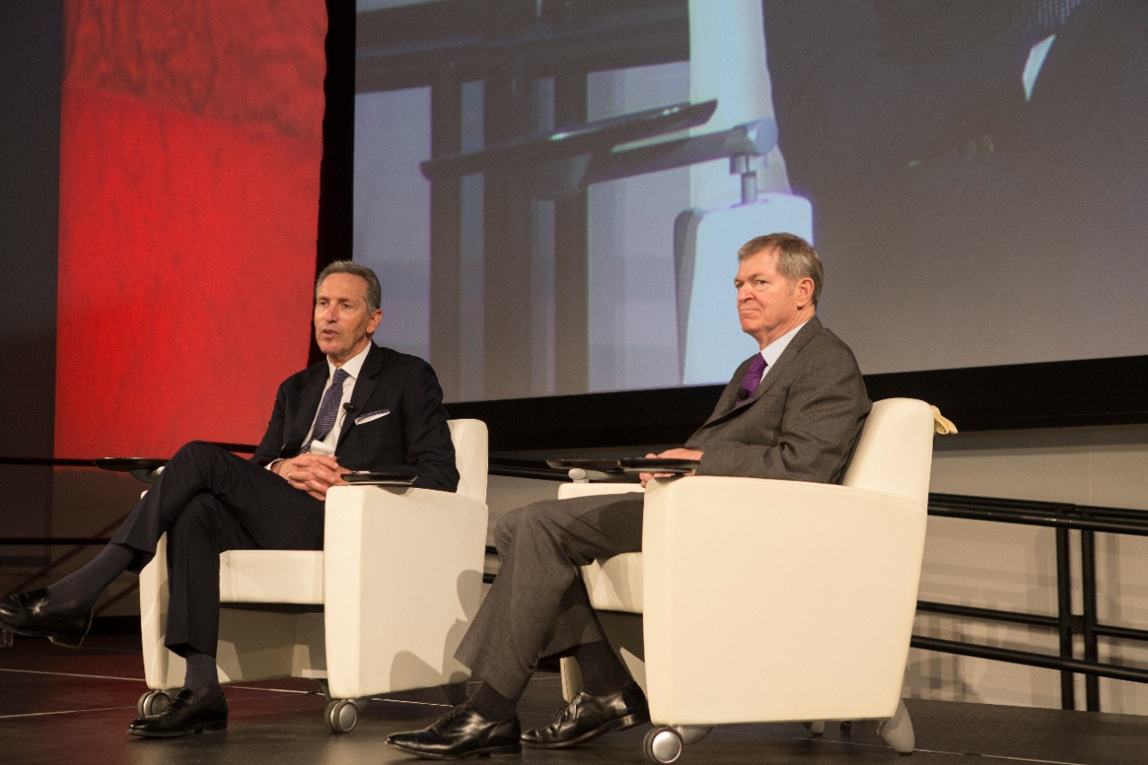 Starbucks Executive Chairman Howard Schultz, left, and former J.C. Penney CEO Myron Ullman III sit in chairs on a stage