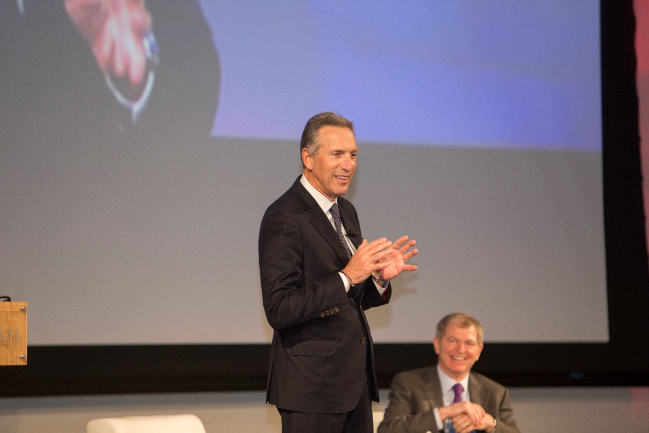 Starbucks Executive Chairman Howard Schultz stands on stage, with former J.C. Penney CEO Myron Ullman III looking on in the background, seated.