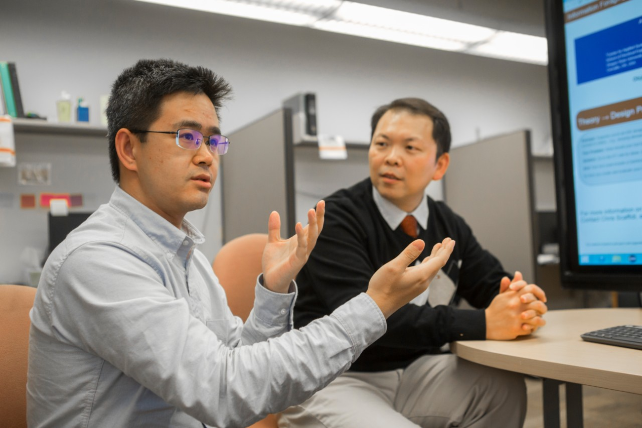UC graduate student Xiaoyu Jin, left, and UC professor Nan Niu talk about their study of Internet foraging. Jin accepted a job in Silicon Valley after he graduates.