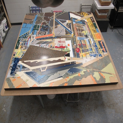 Each piece of the mural is taped down before the entire piece is glued and completed.