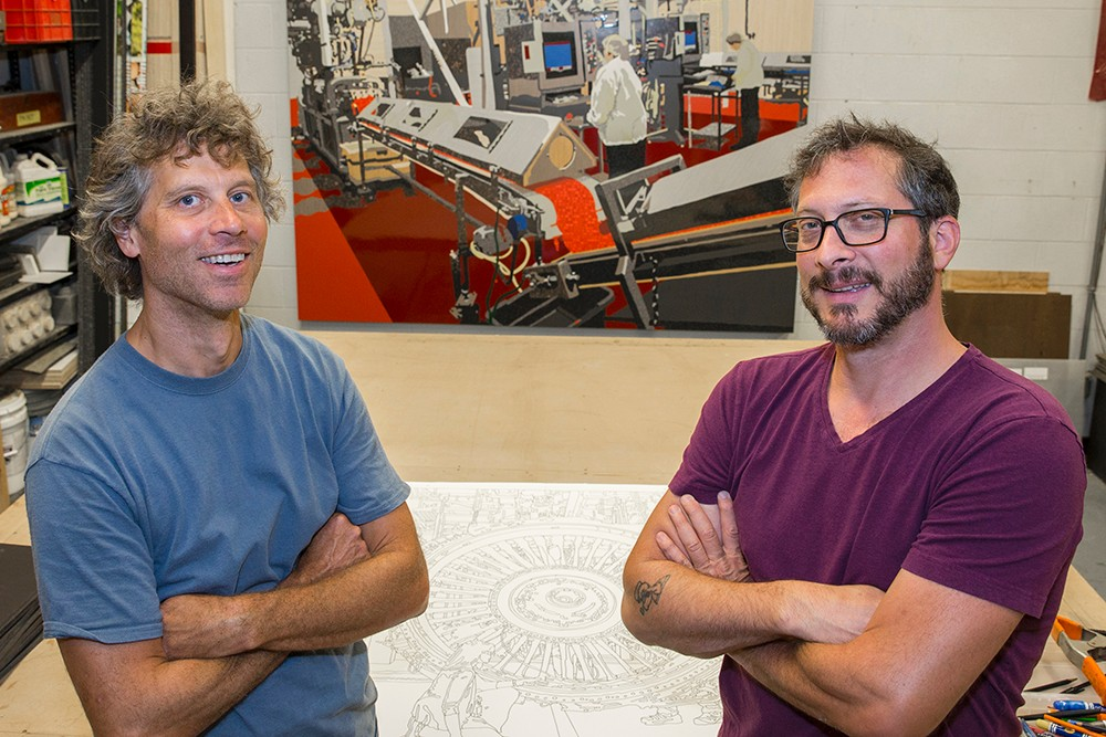 Matt Lynch and Curtis Goldstein pose in front of a line drawing of an engine from G.E. Aviation and a completed mural of the Airheads candy factory.