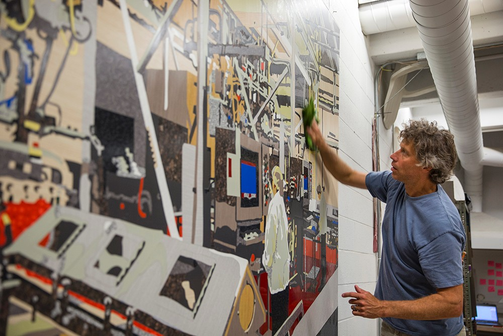 Matt Lynch cleans excess glue off a completed mosaic of the Airheads candy factory.