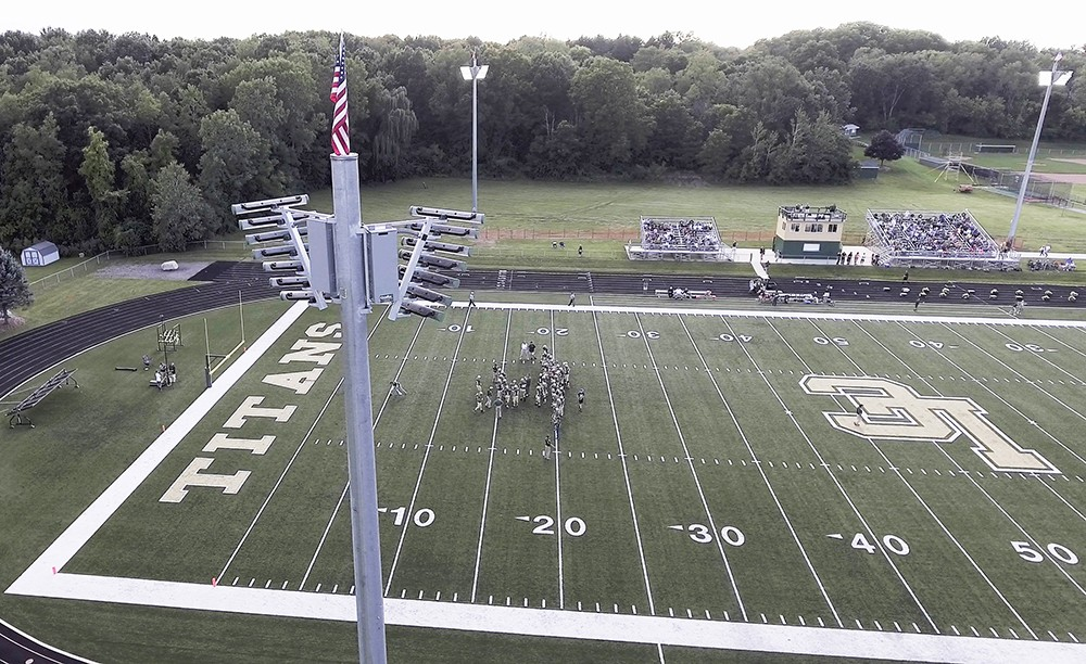 The GameChanger light stands in the foreground of a football field during the daytime.