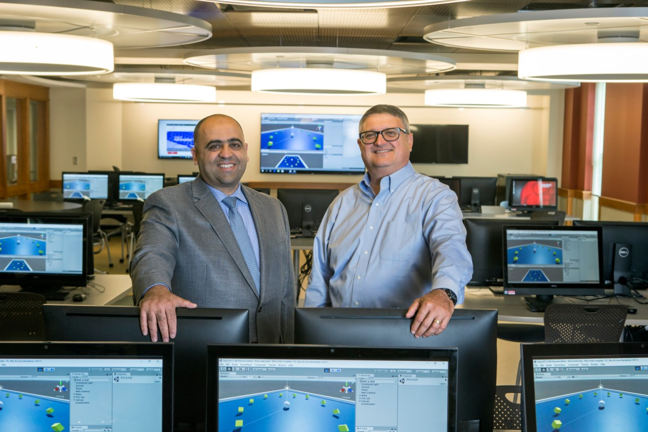 Two men stand in a room filled with computer monitors