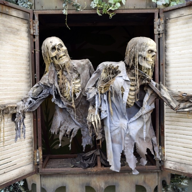 Two skeletons look out of a haunted house window