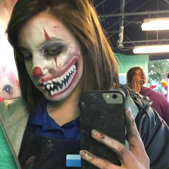 College girl taking a cell-phone selfie of half her face painted like a creepy clown