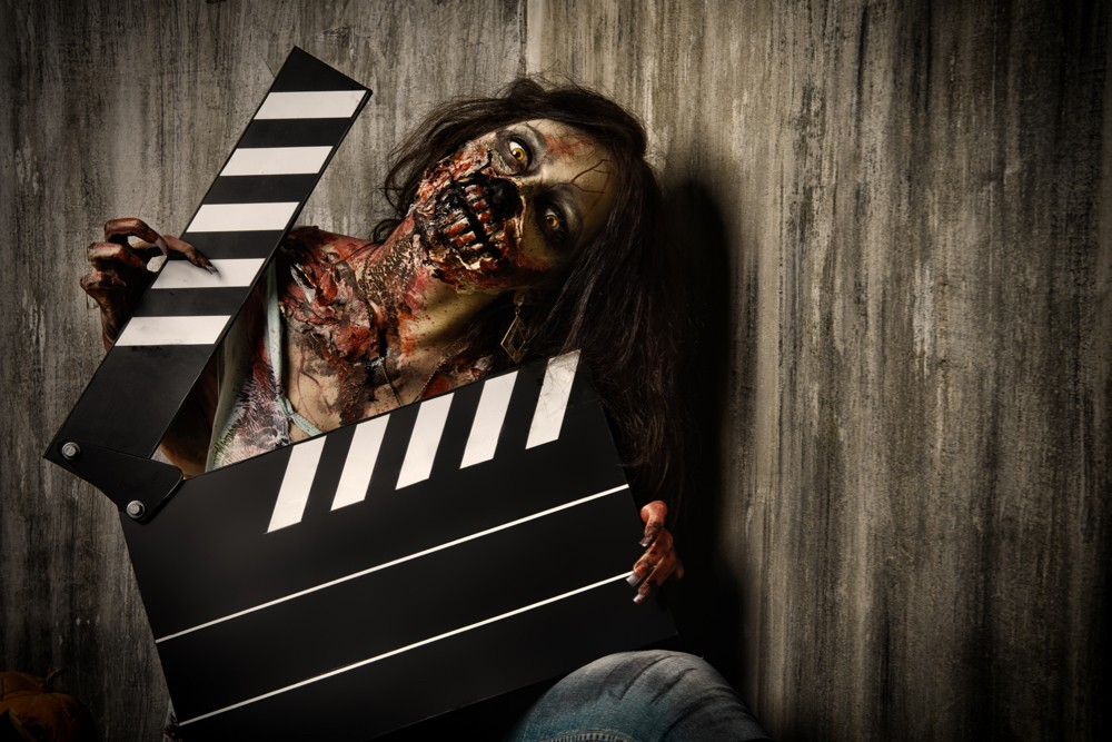 A bloody zombie holds a movie producer's clapboard
