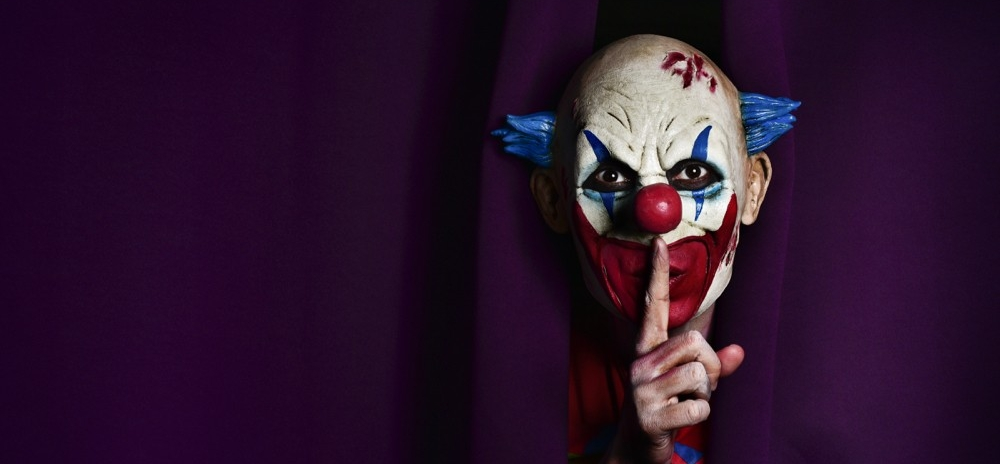 Young boy screams as an evil-looking clown face appears next to him in bed