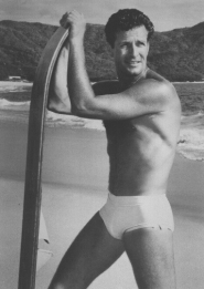 Hugh on the beach wearing his swimsuit and leaning of his surfboard.