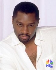 Rodney in a white shirt, looking serious.