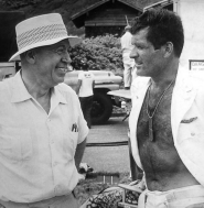 Hugh with his shirt open talking to Otto Preminger