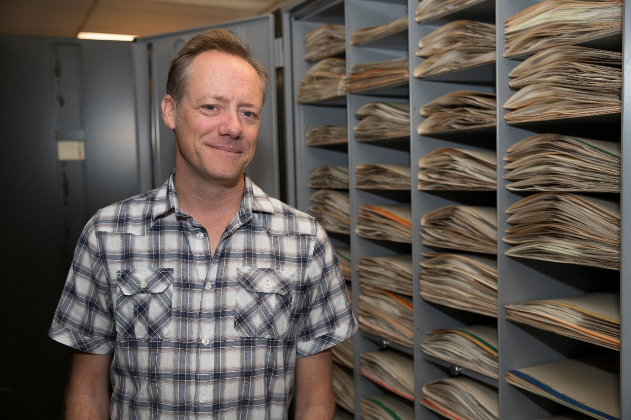 UC biology professor Eric Tepe stands in front of a cabinet full of botanical specimens in the herbarium.