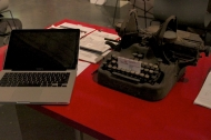 A laptop and an old manual typewriter on a table.