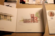 Sketches made by architecture students displayed on table.
