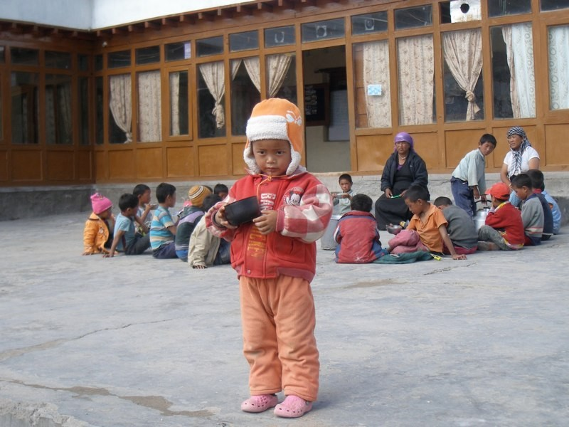 An Indian child breaks away from classmates in the Himalaya.