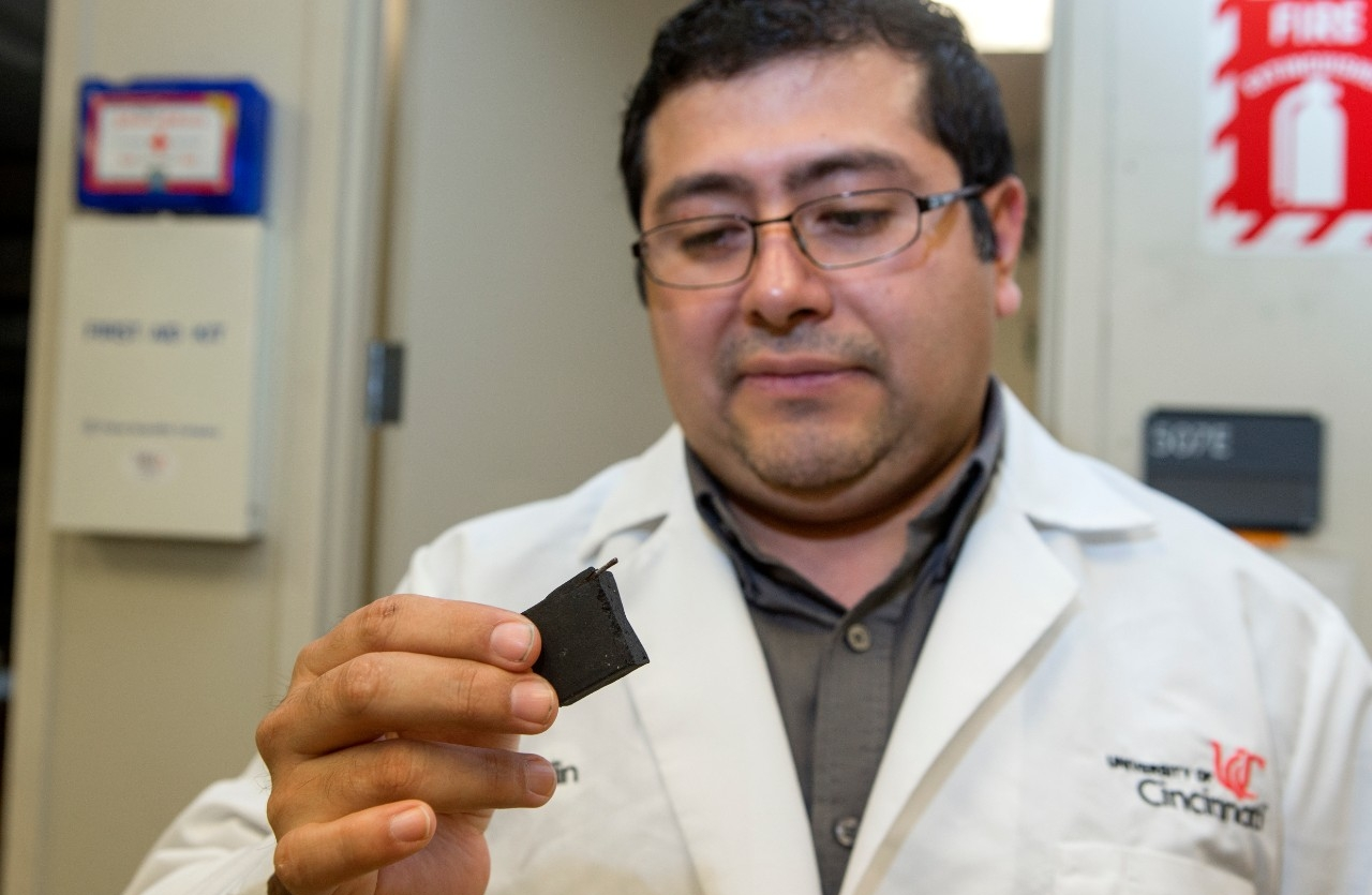 Associate Research Professor Julio Landero Figueroa holds a piece of commercial hookah charcoal that contains a nail. UC researchers found some charcoals contained heavy metals and other toxins.