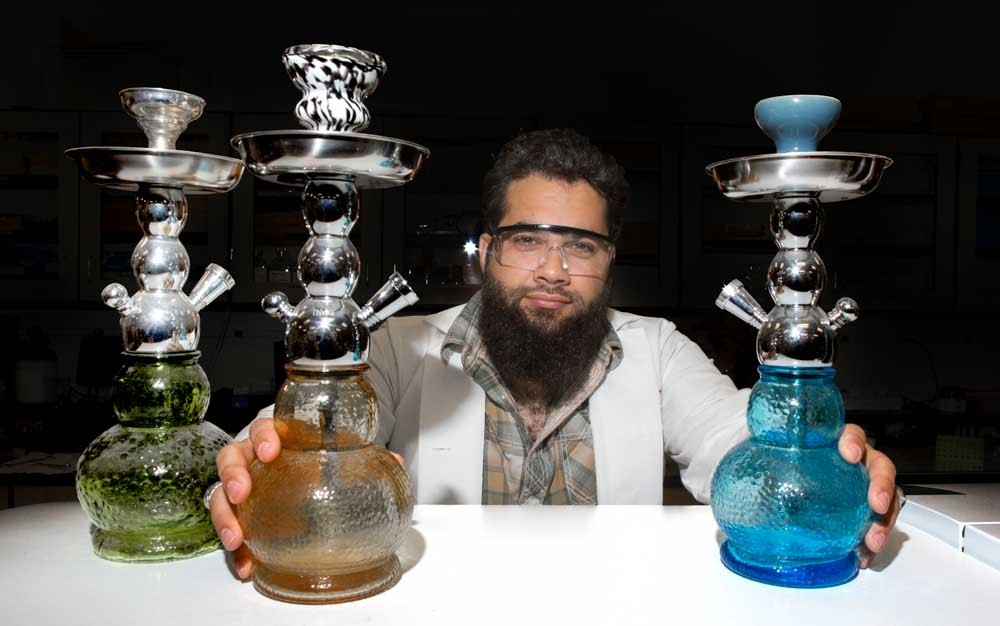 UC graduate student Ryan Saadawi poses with three hookah pipes.