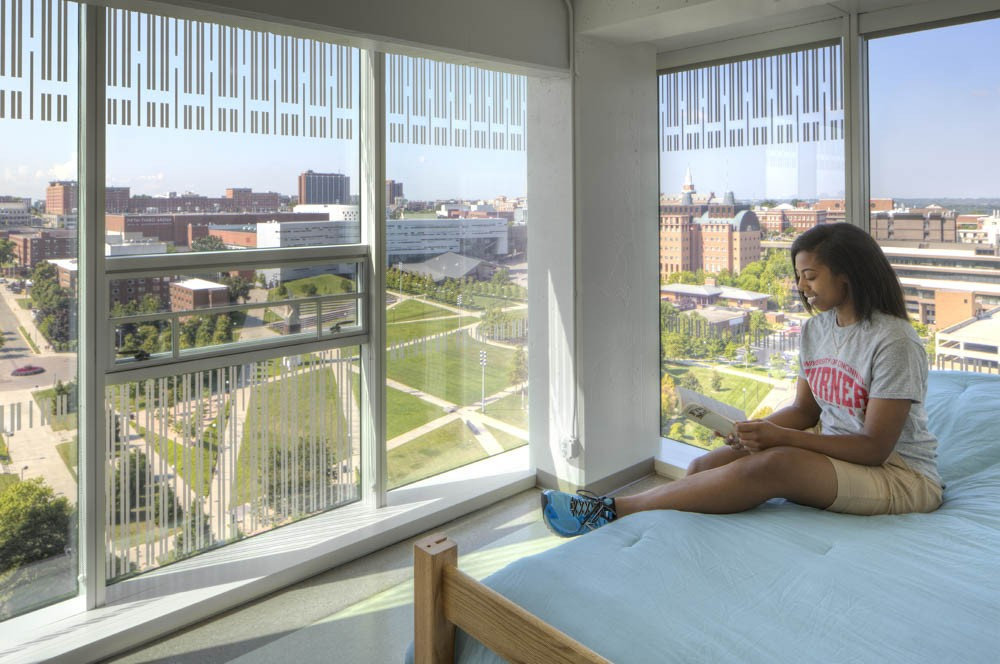 A student sits on her bed, reading in her Morgens Hall dorm room--with wall-to-wall windows, overlooking the campus. Photo/Brad Feinknopf