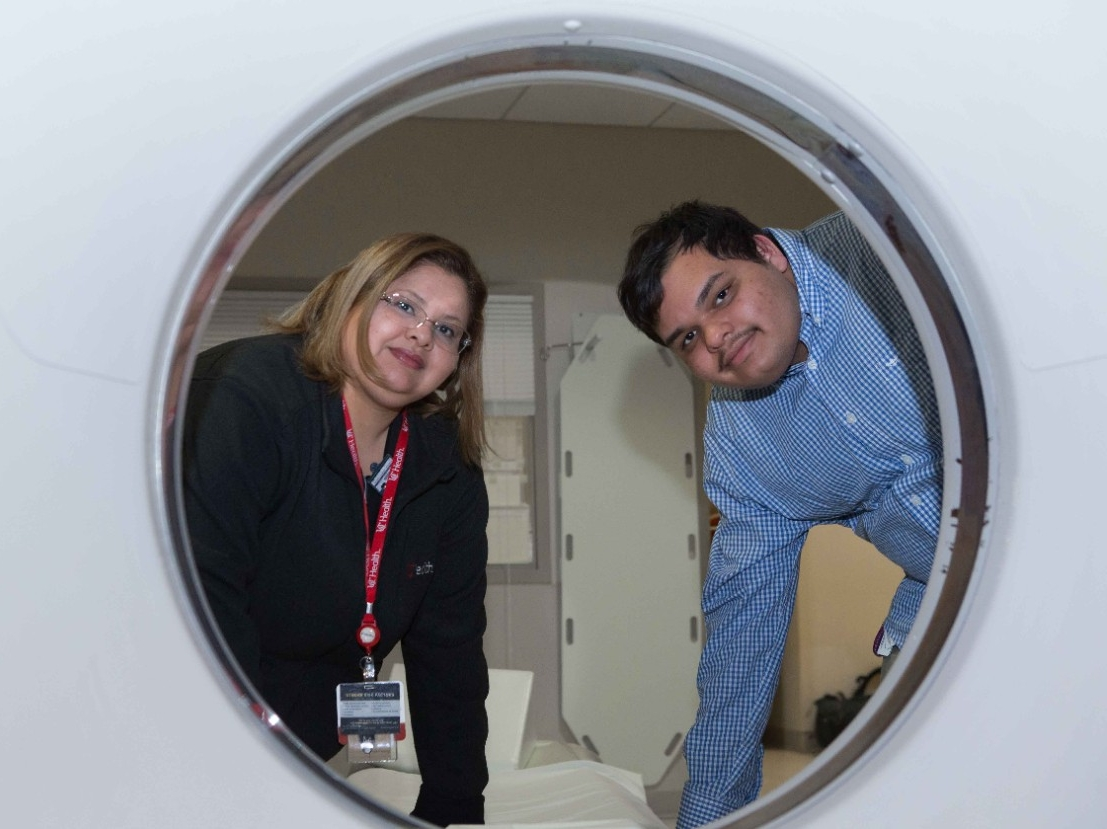 Jessica Rivera and her son, Christopher, pose at the end of a CT machine at West Chester Hospital where she works as a technician.