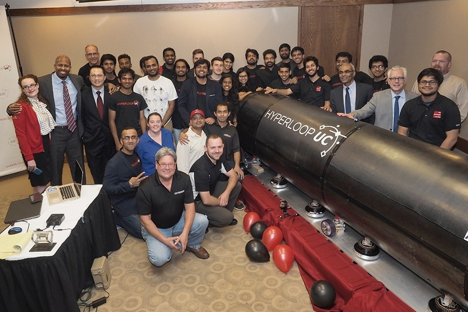 UC students, faculty, administrators and private-sector partners crowd around the Hyperloop UC prototype during the unveiling ceremony.