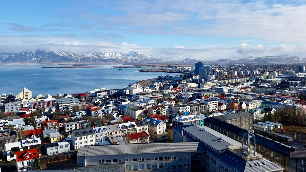Aerial view of colorful rooftops against a blue ocean and mountains in Reykjavik, the capital city of Iceland.photo/Jacob Orkwis