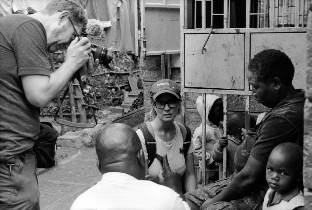 UC photojournalist Sean Hughes takes photos of UC's Adrian Parr as she sits with villagers in Nairobi, Africa.
