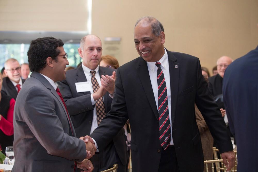 UC President Neville Pinto shakes hands with student body president Bashir Emlemdi