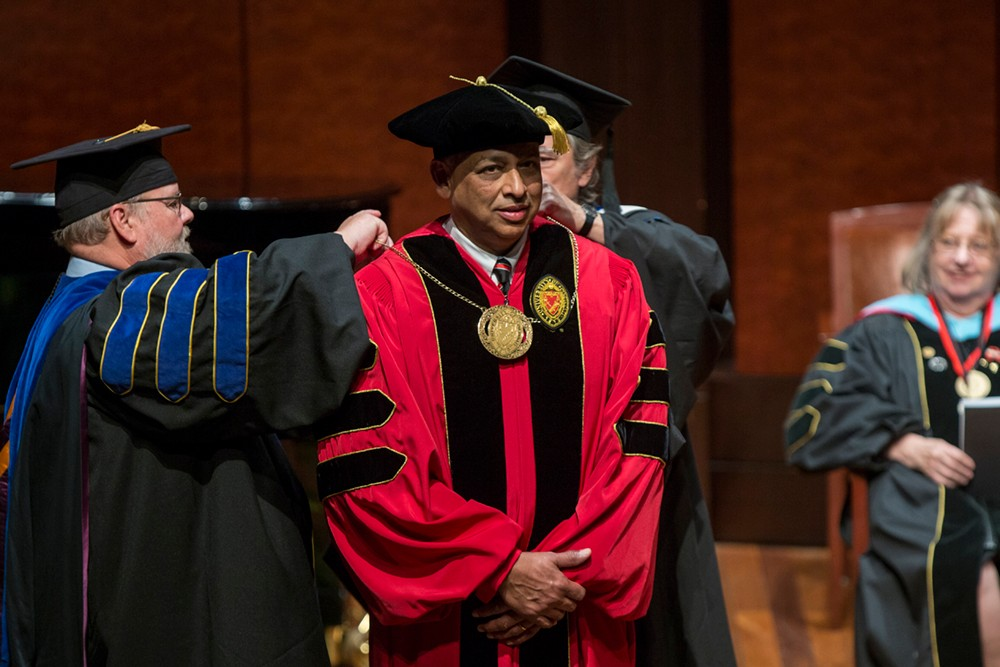 President Neville Pinto receives medal on stage during inauguration