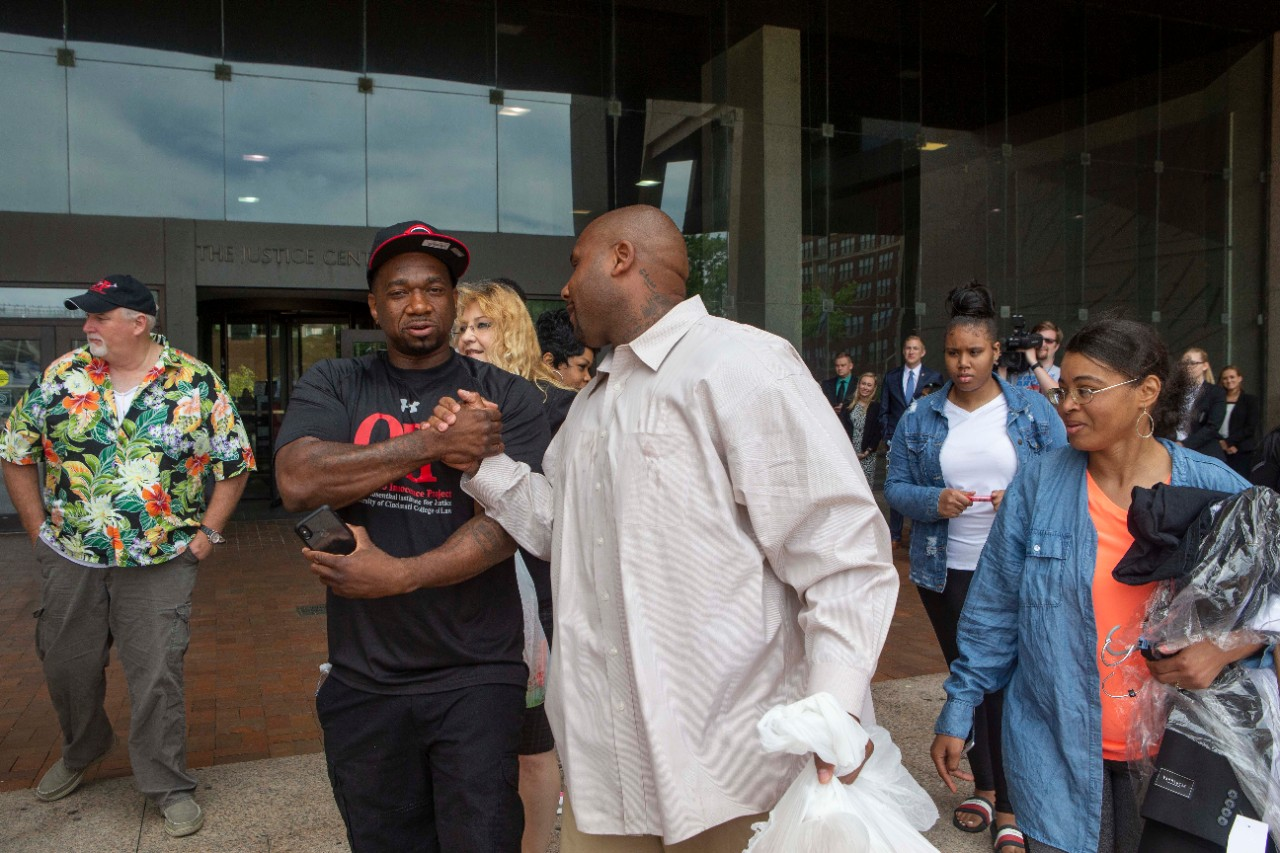 Ohio Innocence Project exonerees Dean Gillispie, far left, and Ru-El Sailor congratulate Christopher Miller on Thursday on the steps of the Cuyahoga County Justice Center. Gillispie and Sailor were released from prison with help from students and faculty at UC's College of Law and its Ohio Innocence Project.