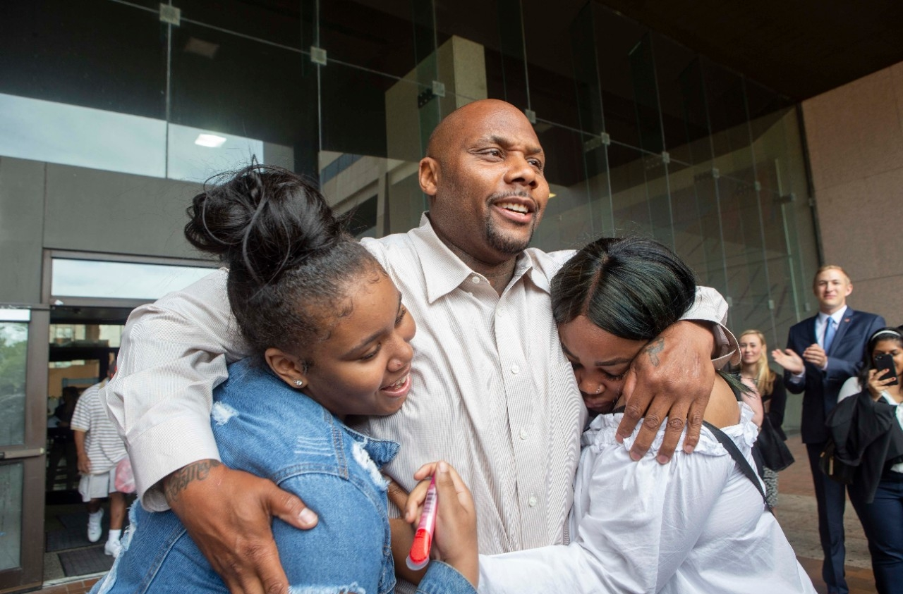 Christopher Miller hugs his daughters De'Nazha, left, and Chareale on Thursday outside the Cuyahoga County Justice Center. Miller was exonerated with help from UC's College of Law after spending 17 years in prison for crimes he did not commit.