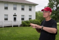 An older gentleman in a T-shirt and ballcap gestures while standing in front of an old Shaker house