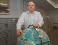 Professor standing next to globe