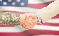 Photo illustration of two in a handshake, one in camoflage, the other a business suit, in front of an American flag