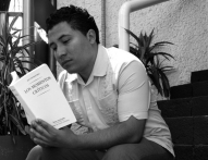 Manuel Iris reads from a book of poetry