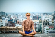 A young man sits cross-legged in a yoga pose on the roof overlooking a city.
