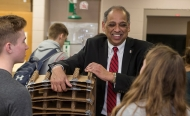The University of Cincinnati's new president, Neville Pinto, smiles and interacts with students in a classroom.
