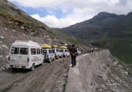 A picturesque scene of mountains with a line of vans working their way along the edge.