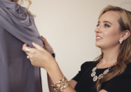 Beautiful, stylish blonde University of Cincinnati alumna adjust some clothing she designed.