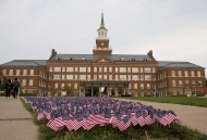 A photo of an iconic University of Cincinnati building, McMicken Hall, with a sea of American flags in front.