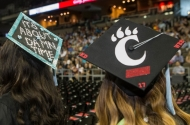 Two graduates' decorated mortarboards at the University of Cincinnati summer commencement