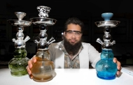 Bearded man sitting in between three glass hookah pipes.