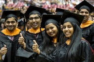 Graduates in caps and gowns give a 'thumbs up' after receiving their degrees.
