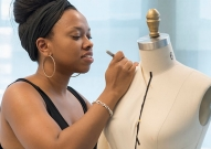A University of Cincinnati alumna Asha Ama Daniels-Henderson stands next to a dress form while designing for Project Runway: All Stars