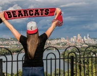 UC student stands with UC banner overlooking city of Cincinnati
